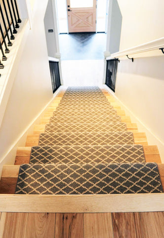 View from the top of a light brown wooden staircase with a blue and white diamond printed carpet down the middle.