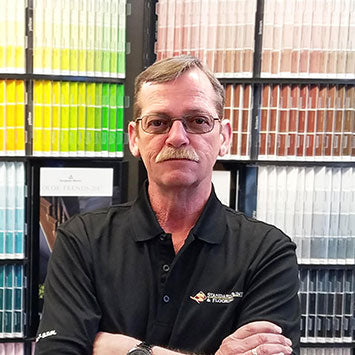Terry Carpenter standing in front of a wall of paint color chips at Standard Paint & Flooring's Richland, WA location.