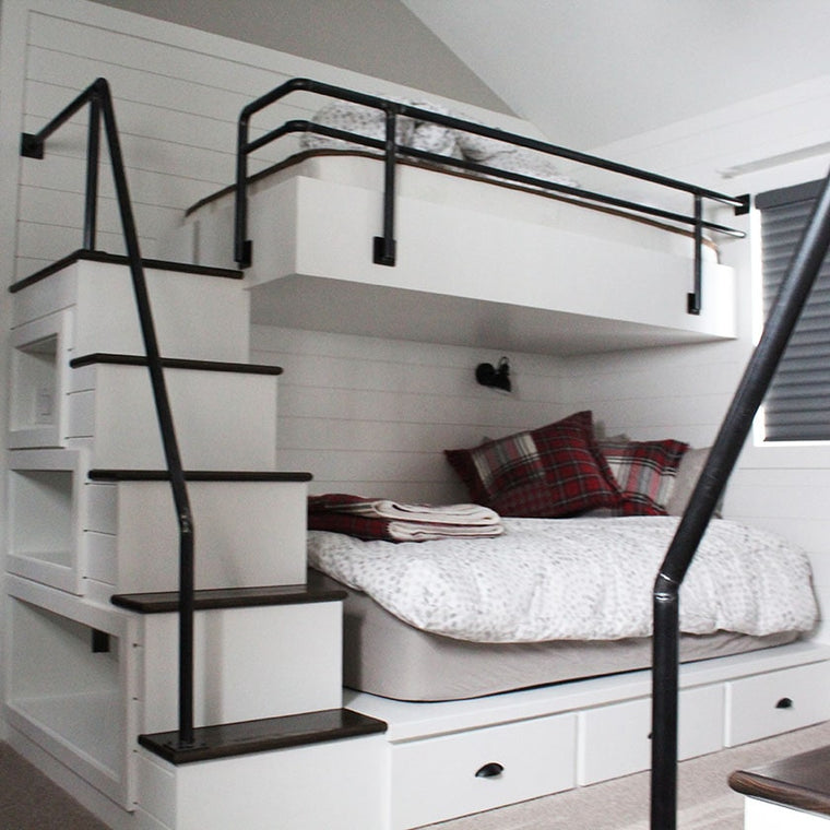 custom white bunk beds, with black railings, and wood stairs by Modern Millwork