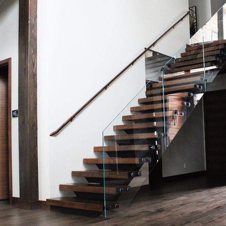 Custom stair case with glass railing, wood banister, and metal detailing by Modern Millwork
