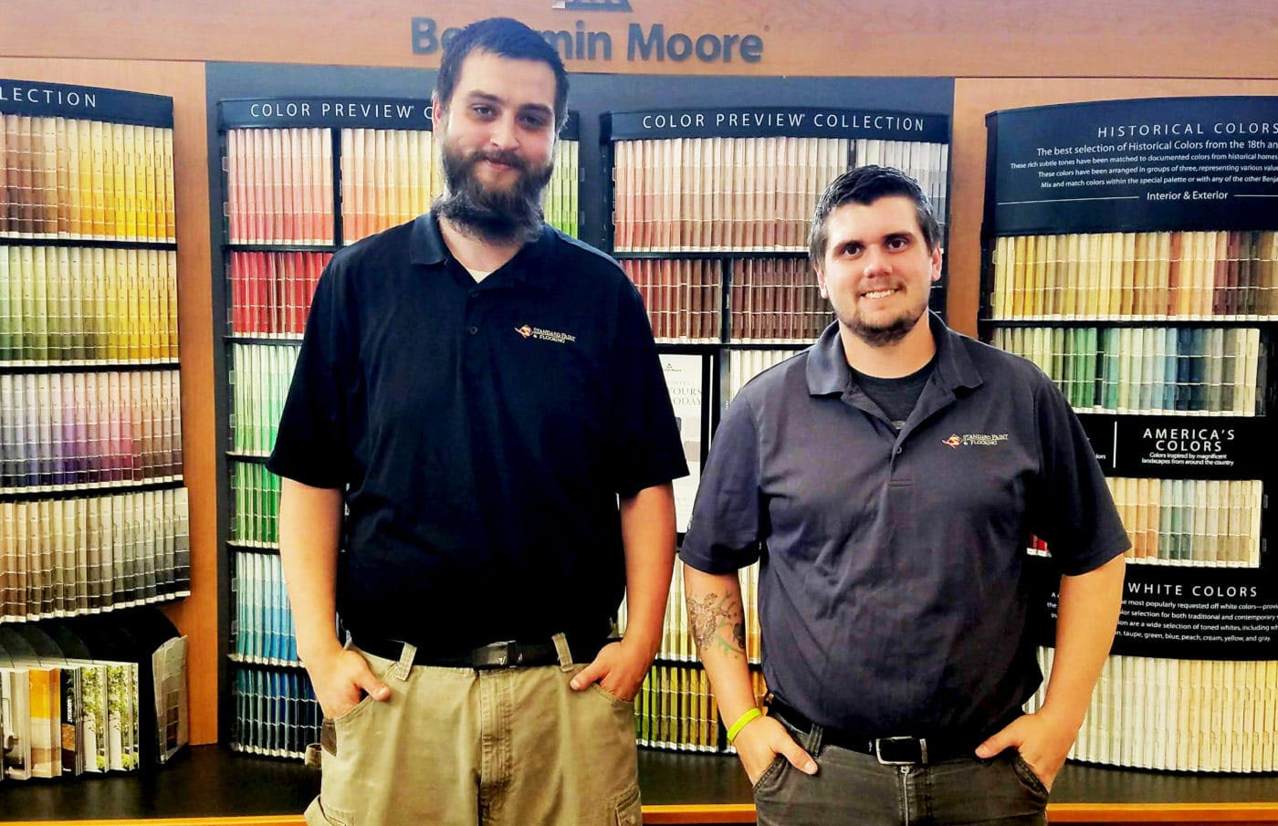 Paint Pros DaKoda and Michael smiling in front of a Benjamin Moore paint color chip display at Standard Paint & Flooring's Wenatchee location.
