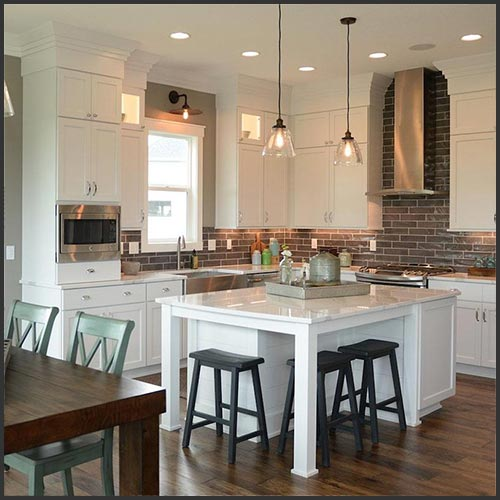 A kitchen with white cabinets, a white island with black stools, dark hardwood flooring and dark grey subway tile for a backsplash.
