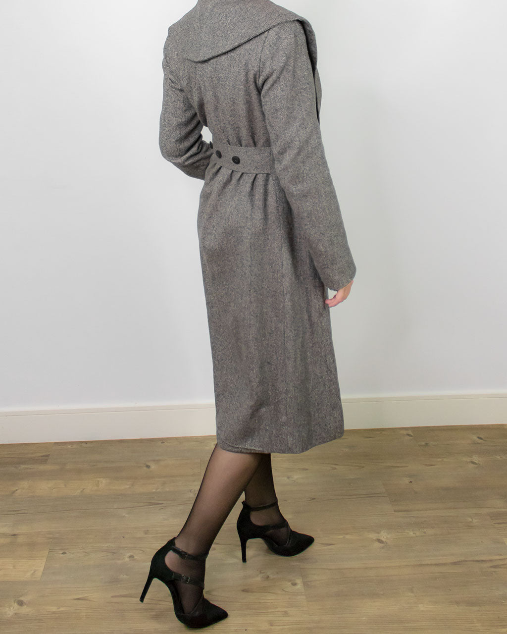 Back view of maxi skater tailored fit and flare coat by ADKN with belt and corozo buttons detail and a wide collar