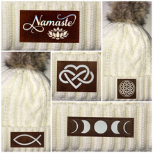 Load image into Gallery viewer, Beanies - Ivory Plush, Blanket Lined Cable Knit, Pom Pom Beanie with The Eye of Horus, Ganesha, Ichthus/Christian Fish, Infinite Love, Buddha, Namaste, Puppy Love, Flower of Life, Moons, Lotus, Tree of Life, Cannabis, Mushrooms and Coffee