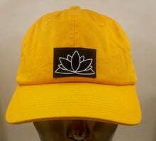 Load image into Gallery viewer, Buddha Gear Buddha Lids Buddha wear Mustard dad hat with handmade lotus symbol  The lotus has long been regarded as sacred by many of the world's religions, especially in India and Egypt, where it is held to be a symbol of the Universe itself. Rooted in the mud, the lotus rises to blossom clean and bright, symbolizing purity and resurrection  In Buddhist symbolism the lotus is symbolic of purity of the body, speech, and mind as while rooted in the mud, its flowers blossom on long stalks as if floating above
