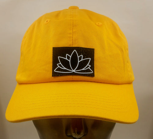 Buddha Gear Buddha Lids Buddha wear Mustard dad hat with handmade lotus symbol  The lotus has long been regarded as sacred by many of the world's religions, especially in India and Egypt, where it is held to be a symbol of the Universe itself. Rooted in the mud, the lotus rises to blossom clean and bright, symbolizing purity and resurrection  In Buddhist symbolism the lotus is symbolic of purity of the body, speech, and mind as while rooted in the mud, its flowers blossom on long stalks as if floating above