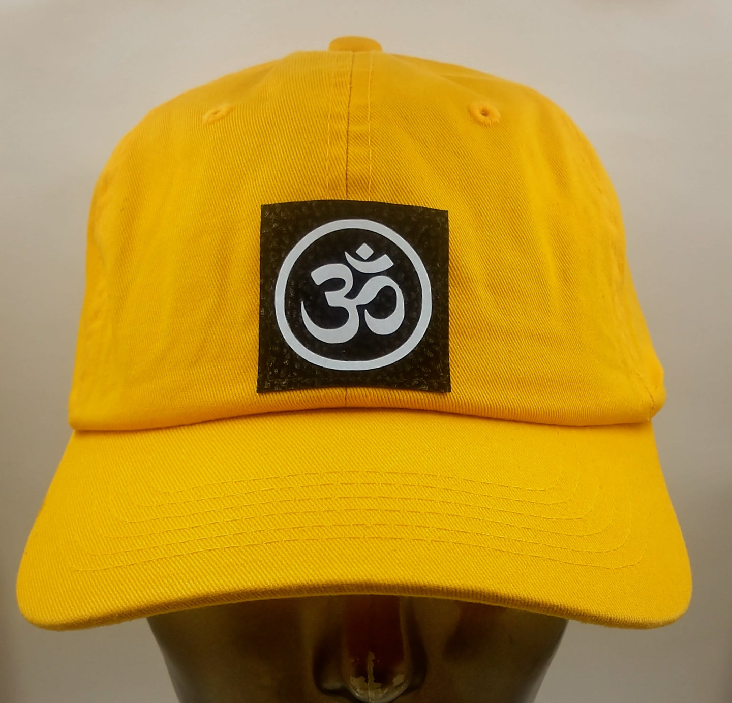 Buddha gear Buddha lids Mustard dad hat with hand made ohm symbol  Ohm is a sacred sound and a sacred spiritual symbol in Hinduism, that signifies the essence of the ultimate reality, consciousness or Atman (soul). Some believe it is the sound of creation.
