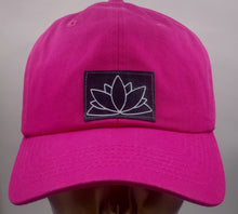 Load image into Gallery viewer, Buddha gear Buddha lids Hot pink dad hat with handmade lotus patch  The lotus has long been regarded as sacred by many of the world's religions, especially in India and Egypt, where it is held to be a symbol of the Universe itself. Rooted in the mud, the lotus rises to blossom clean and bright, symbolizing purity and resurrection  In Buddhist symbolism the lotus is symbolic of purity of the body, speech, and mind while rooted in the mud, its flowers blossom on long stalks as if floating above the muddy wate