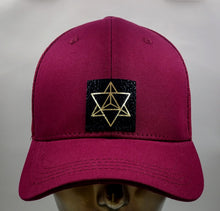 Load image into Gallery viewer, Buddha gear Buddha lids Buddha wear Buddha clothing Burgundy snapback with hand made Merkaba symbol   The word Merkaba is actually composed of three separate words: Mer, which means light, Ka, which means spirit and Ba, which means Body. Put together, these three words connote the union of spirit with the body, surrounded by light. The symbol, which takes the shape of a star, is believed to be a divine vehicle made entirely of light and designed to transport or connect the spirit and body to higher realms.