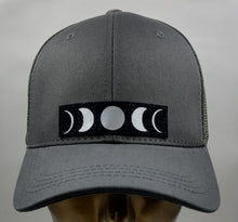Load image into Gallery viewer, Buddha gear Buddha lids Buddha wear Grey snapback with handmade moon symbol   Who isn't mesmerized by the moon? the Moon inhabits the landscapes of the soul, emotions, and dream life 🌕❤️  The moon is a feminine symbol, universally representing the rhythm of time as it embodies the cycle. The phases of the moon symbolize immortality and eternity, enlightenment or the dark side of Nature herself.