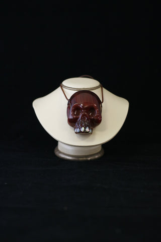 Red handblown glass skull with opal teeth made by Carsten Carlisle