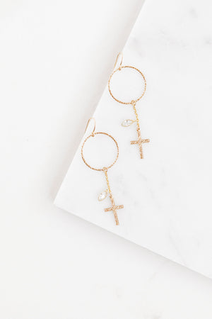 Find the perfect pair of earrings you're looking for from Charme Silkiner! These gold hoop drop earrings with a floral cross and cz bezel are seriously stunning. Perfect to dress or dress down any outfit the Graci Earrings are the perfect must have for everyone!