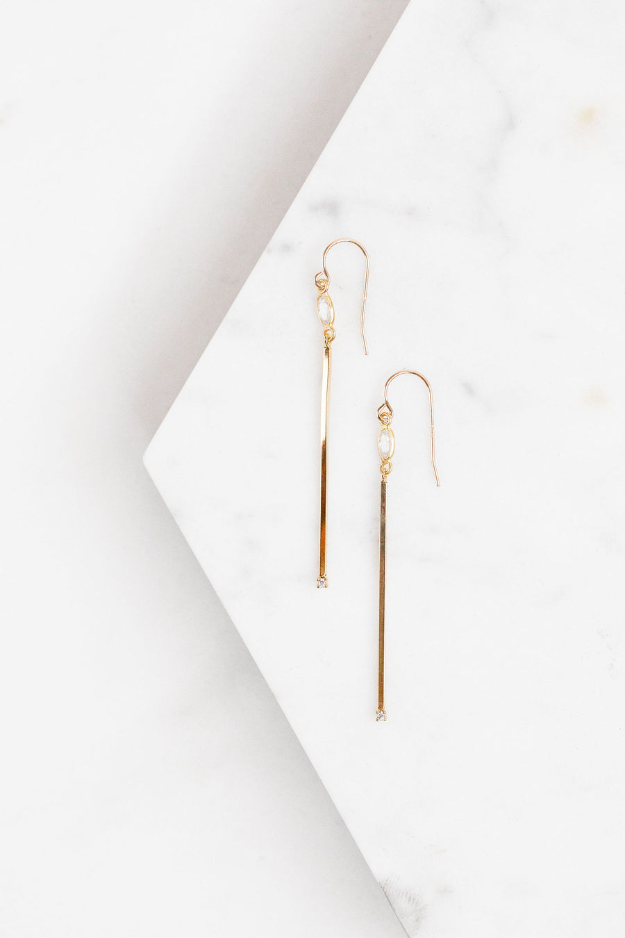 Find the perfect pair of earrings you're looking for from Charme Silkiner! These gold and CZ bezel drop earrings are stunning with their narrow bar and CZ accents. Perfect to dress or dress down any outfit the Vanna Earrings are the perfect must have for everyone!