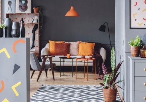A bachelor pad painted in beautiful deep tones with many pop of color to brighten, and add fun to the space. Cool gray walls, with pops of orange, white, yellow, and burgundy.