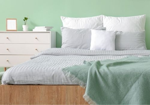 Bedroom painted in a soft mint green with white and grey accent pillows and duvet. A portrait of a room decorated in Spa Day inspired colours.