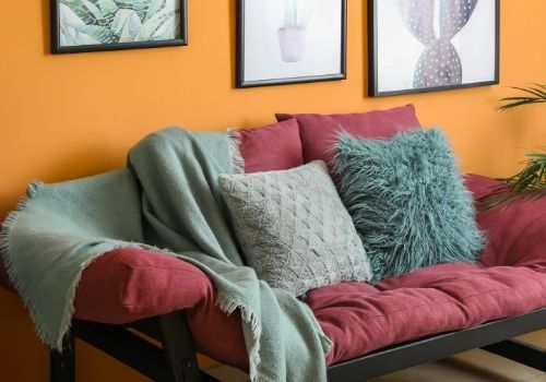 Wall painted orange with a modern burgundy couch against the wall, and throw pillows and blankets of grey and teal. These colours are spicy, and full of flavor.