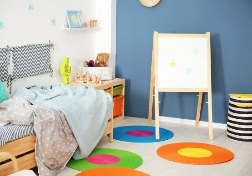 Kids room painted with a blue/gray accent wall and many pop of colour.