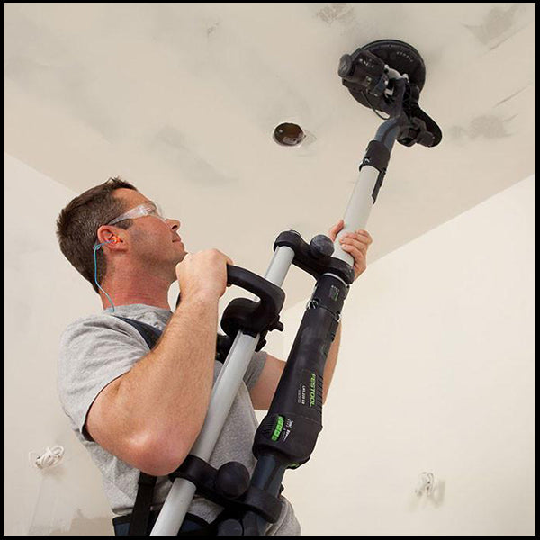 A man using the Festool planex drywall sander in a residential area, available at Clement's Paint in Austin, TX.