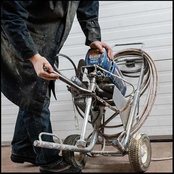 A man with a Graco paint sprayer, available at Clement's Paint in Austin, TX.