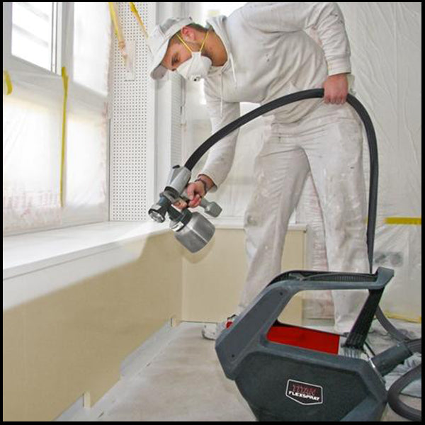 A man using a titan paint sprayer in a home, available at Clement's Paint in Austin, TX.