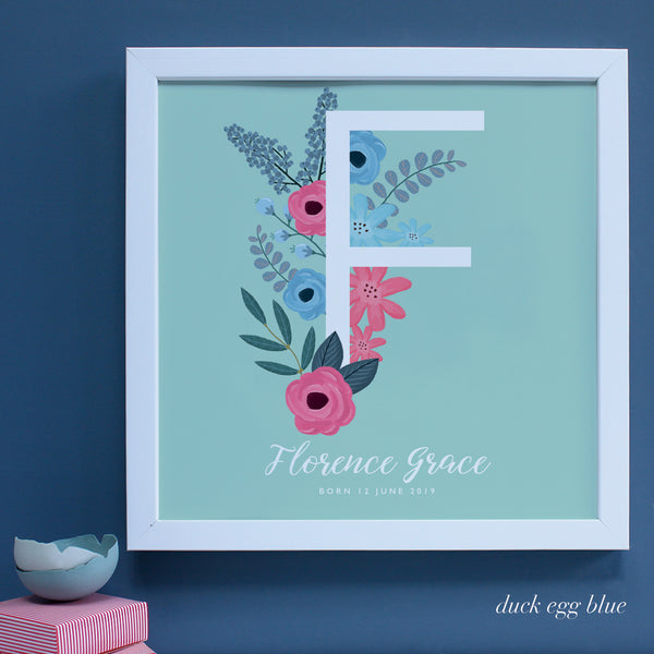 Large white framed New Baby present with letter F on duck egg blue background.