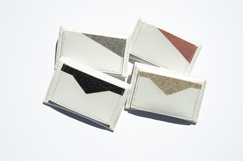 Back of four white geometric and notch cardholders.