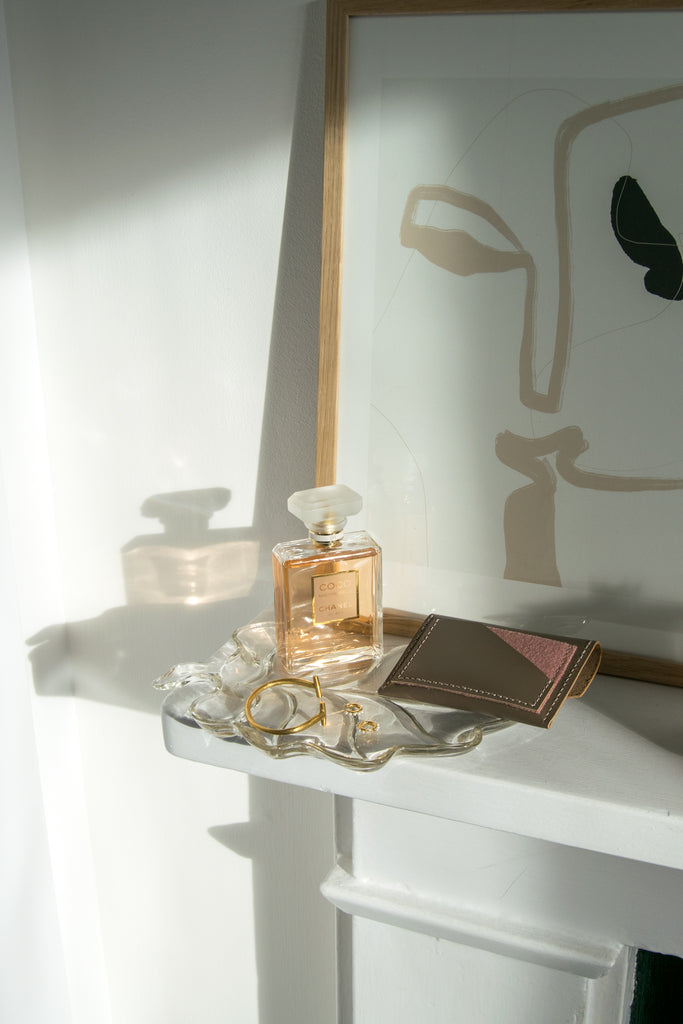 Taupe Leather Card Holder on Glass Tray with Jewelry and Perfume