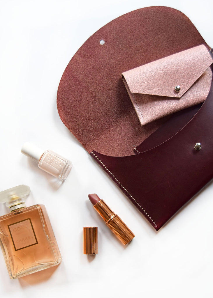 Bordeaux Clutch with Pink Card Holder pictured with lipstick, nail polish and perfume.