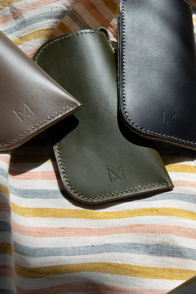 Back detail shot of leather sunglasses sleeves on striped linen.