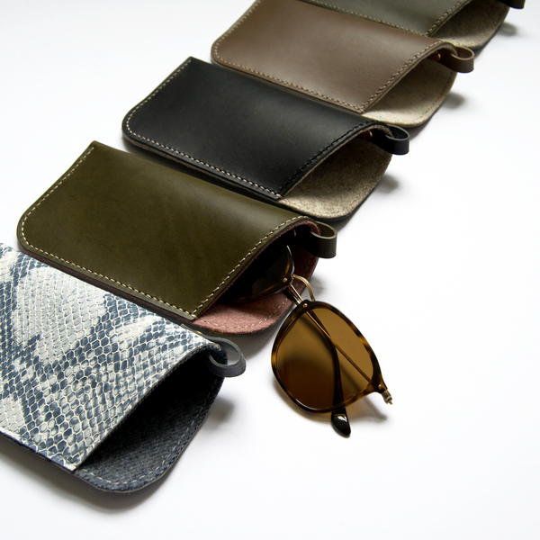 Five leather sunglasses sleeves arranged diagonally with a pair of sunglasses.