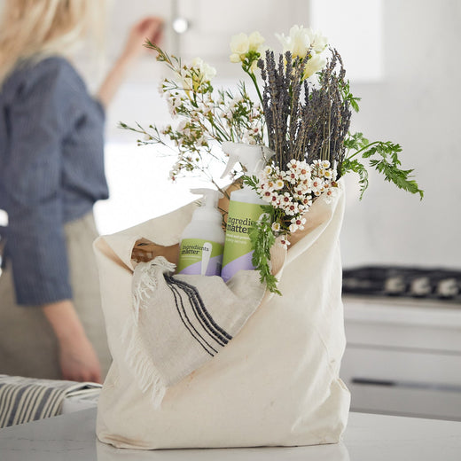 cotton tote bag filled with wildflower bouquet, dish cloth, bottle of foaming hand soap, and all-purpose spray cleaner