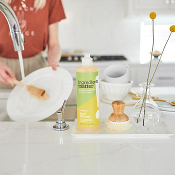 woman washing dishes with a wooden dish scrubbing wand and a bottle of dishwashing liquid and dish scrubber with wooden handle on counter top