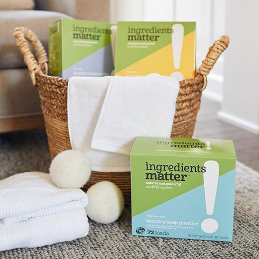 wicker laundry basket, folded towels, two wool dryer balls, and three boxes of laundry soap powder