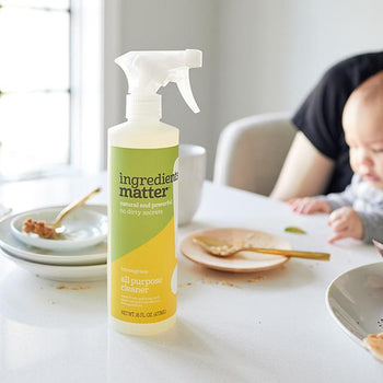 bottle of all-purpose cleaner spray dining table with used dishes and utensils, person holding a baby, and window letting in sunshine