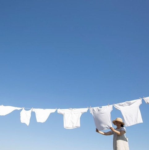 Woman hanging white tshirts on a clothes line