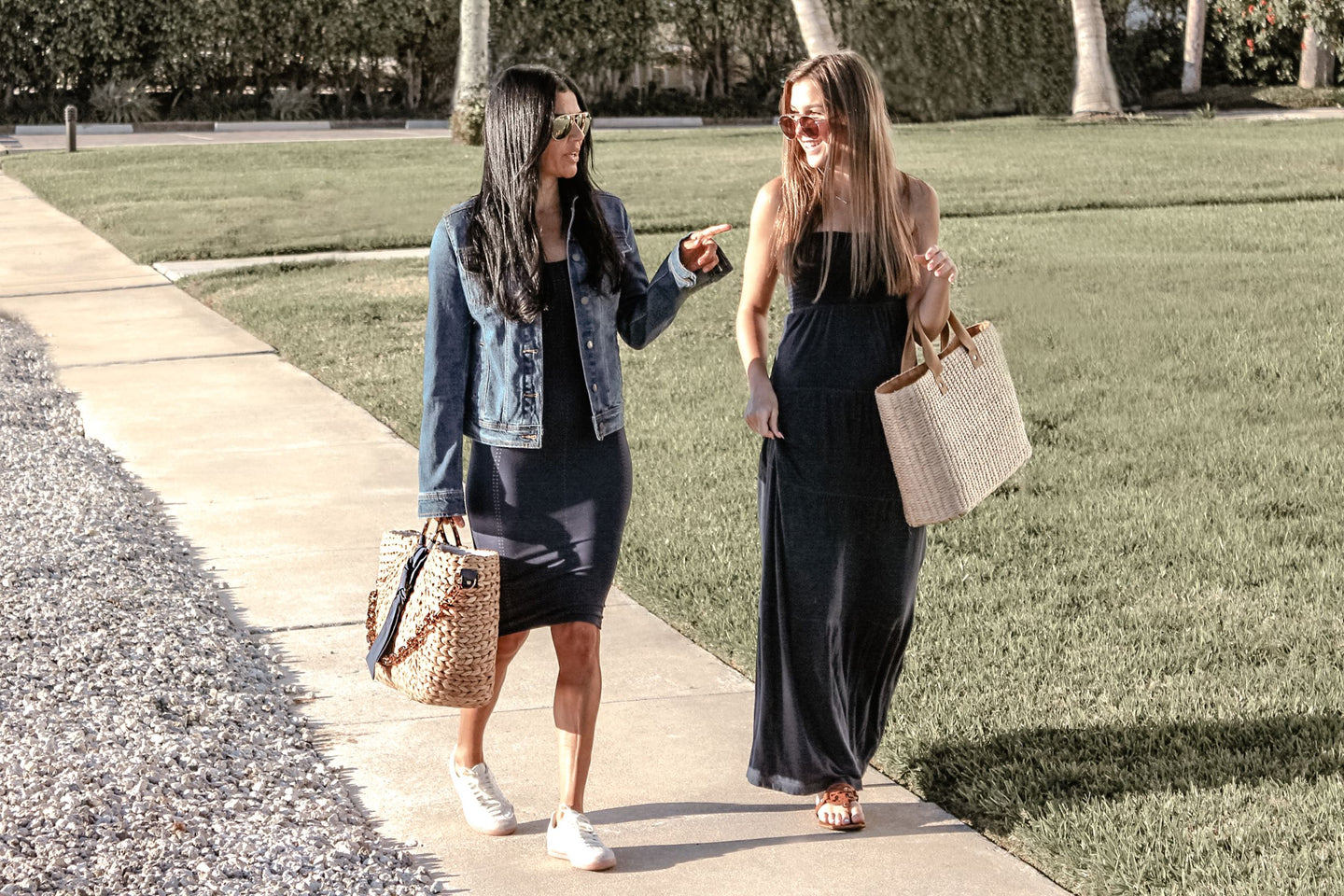 two girls walking down sidewalk carrying straw tote bags