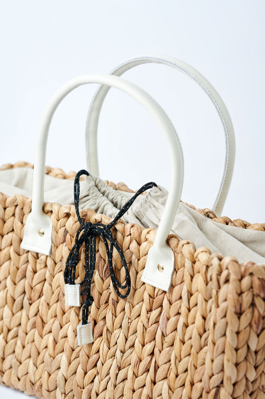 close-up of top of medium natural hyacinth straw tote with linen cinch top