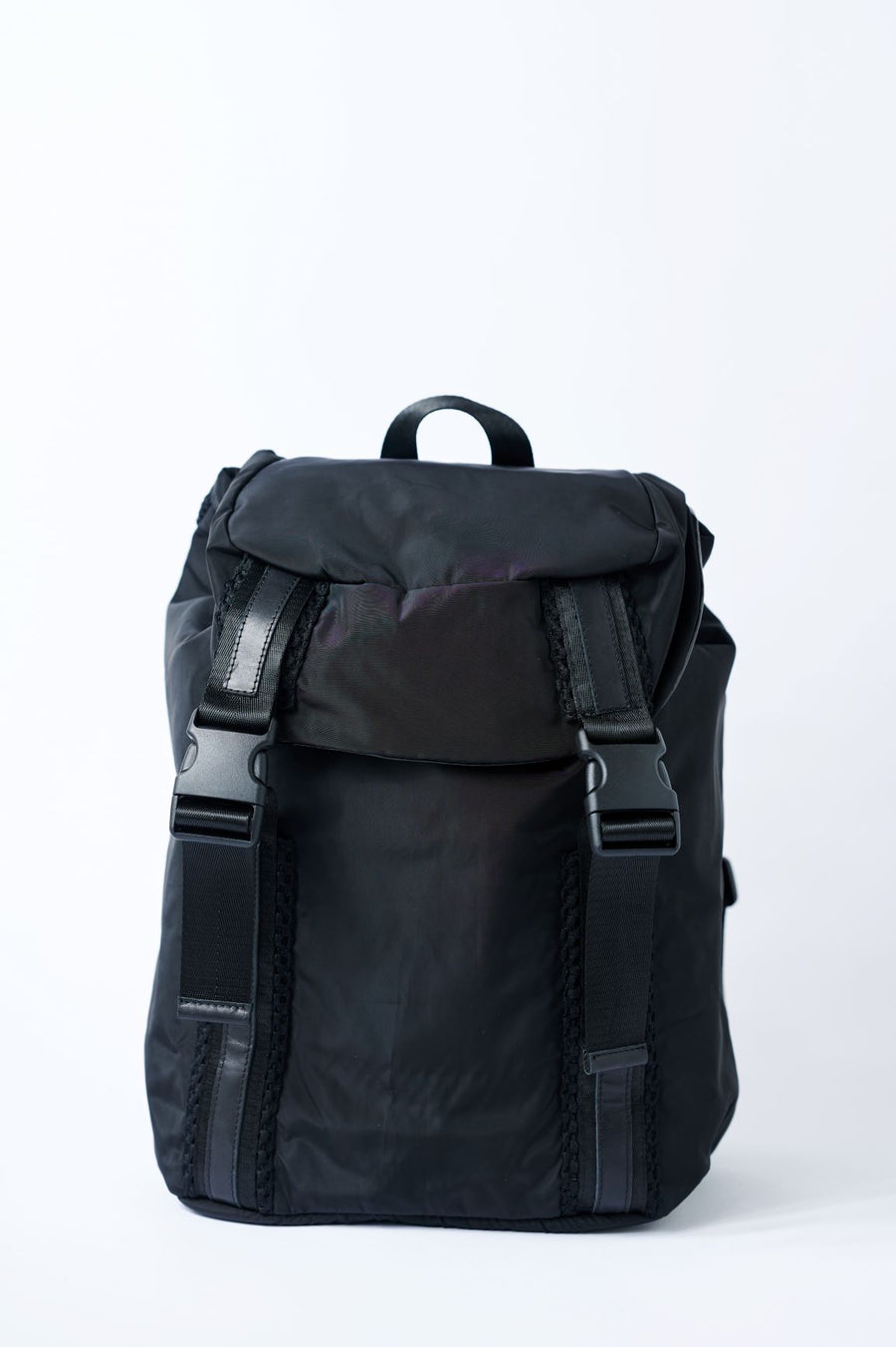 Black nylon flap top backpack with mesh and leather trim details and glossy black lining.
