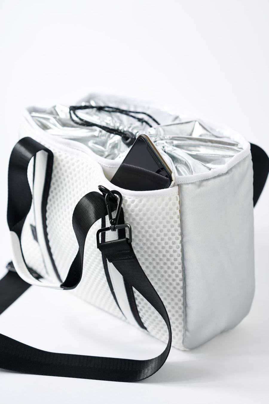 close up of side pocket on small white mesh tote with crossbody strap