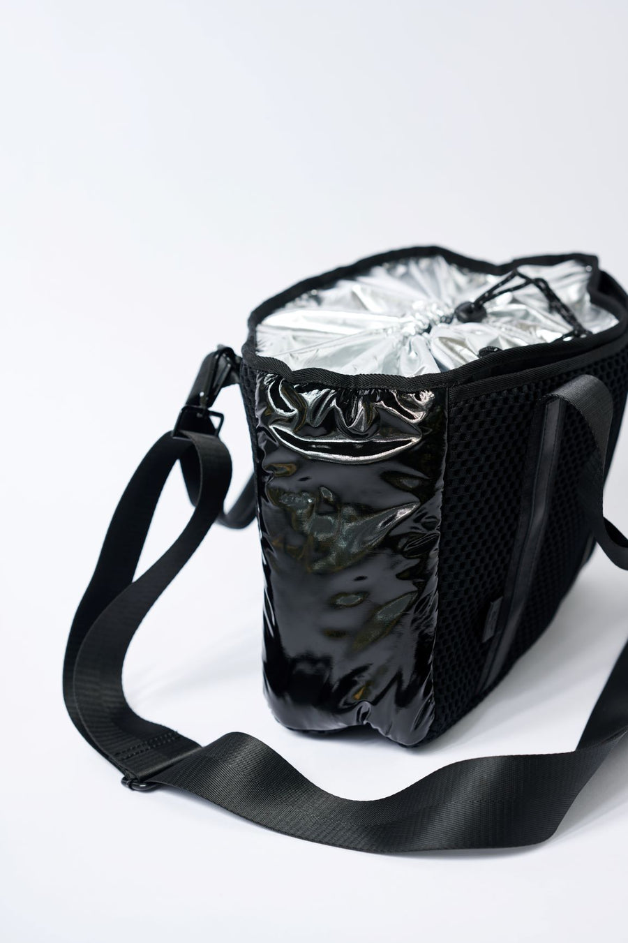 side view of small black mesh tote with crossbody strap