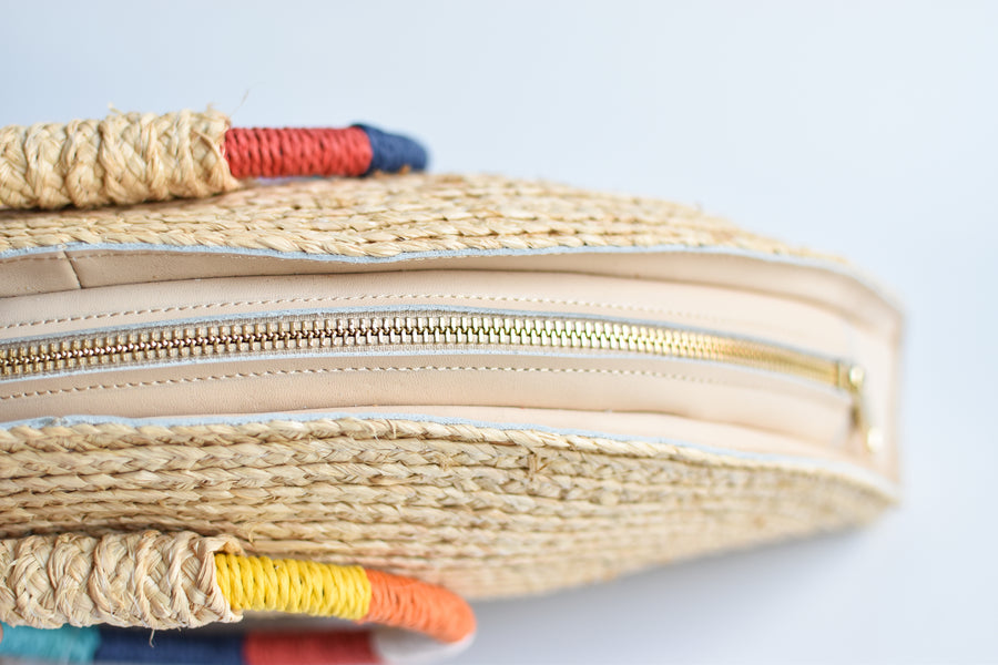 Top view of natural raffia straw half-moon clutch with rainbow colored wrapped circle handle and leather sides.