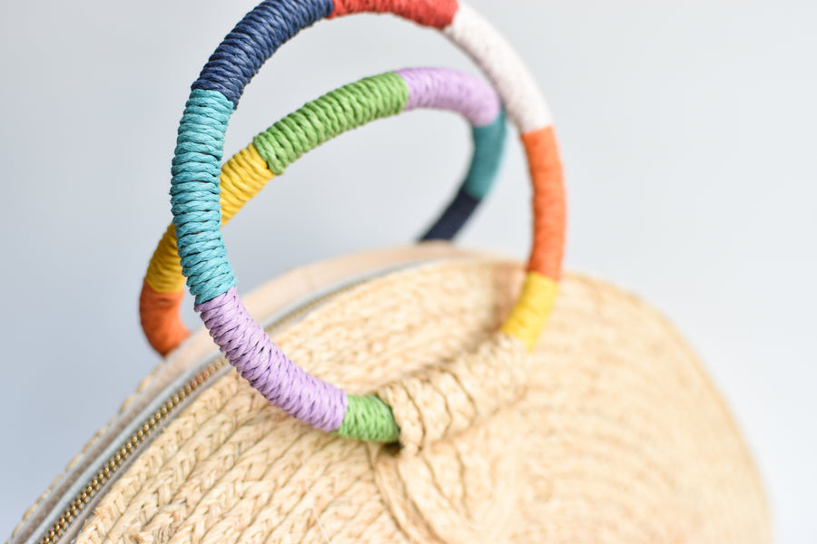 Close up of rainbow colored wrapped circle handles on natural raffia straw half-moon clutch with leather sides.