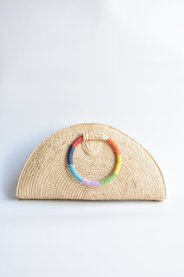 Natural raffia straw half-moon clutch with rainbow colored wrapped circle handle and leather sides.