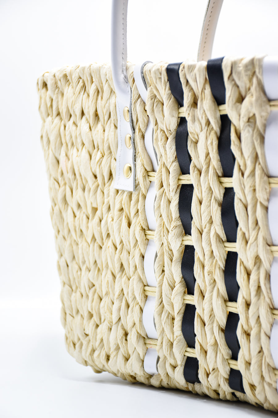 Close up of small woven straw tote bag laced with black and white leather.