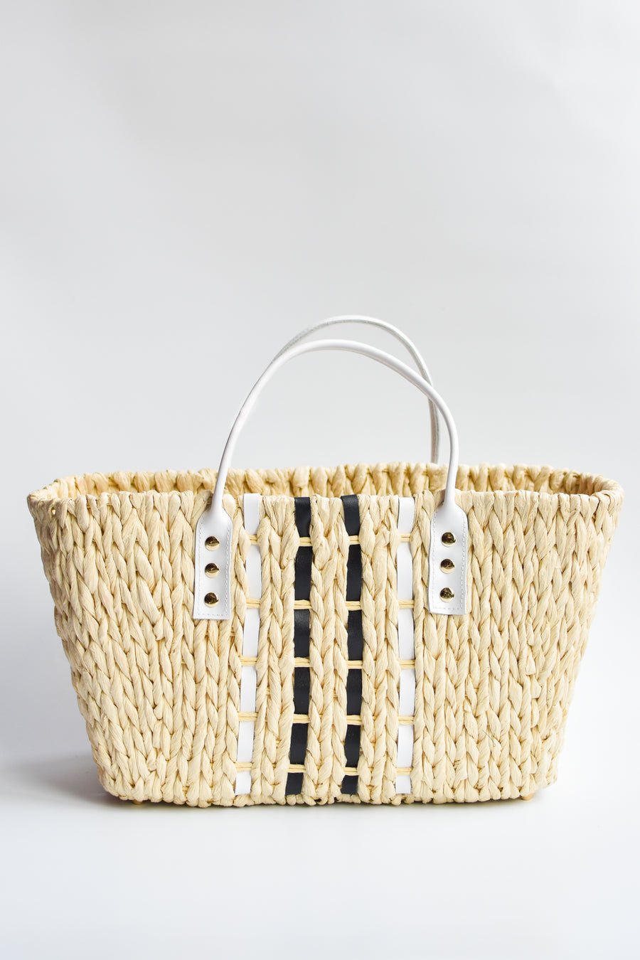 Small woven straw tote bag laced with black and white leather.