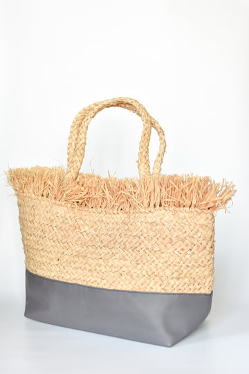 Natural raffia straw tote with linen lining and gray color block base.