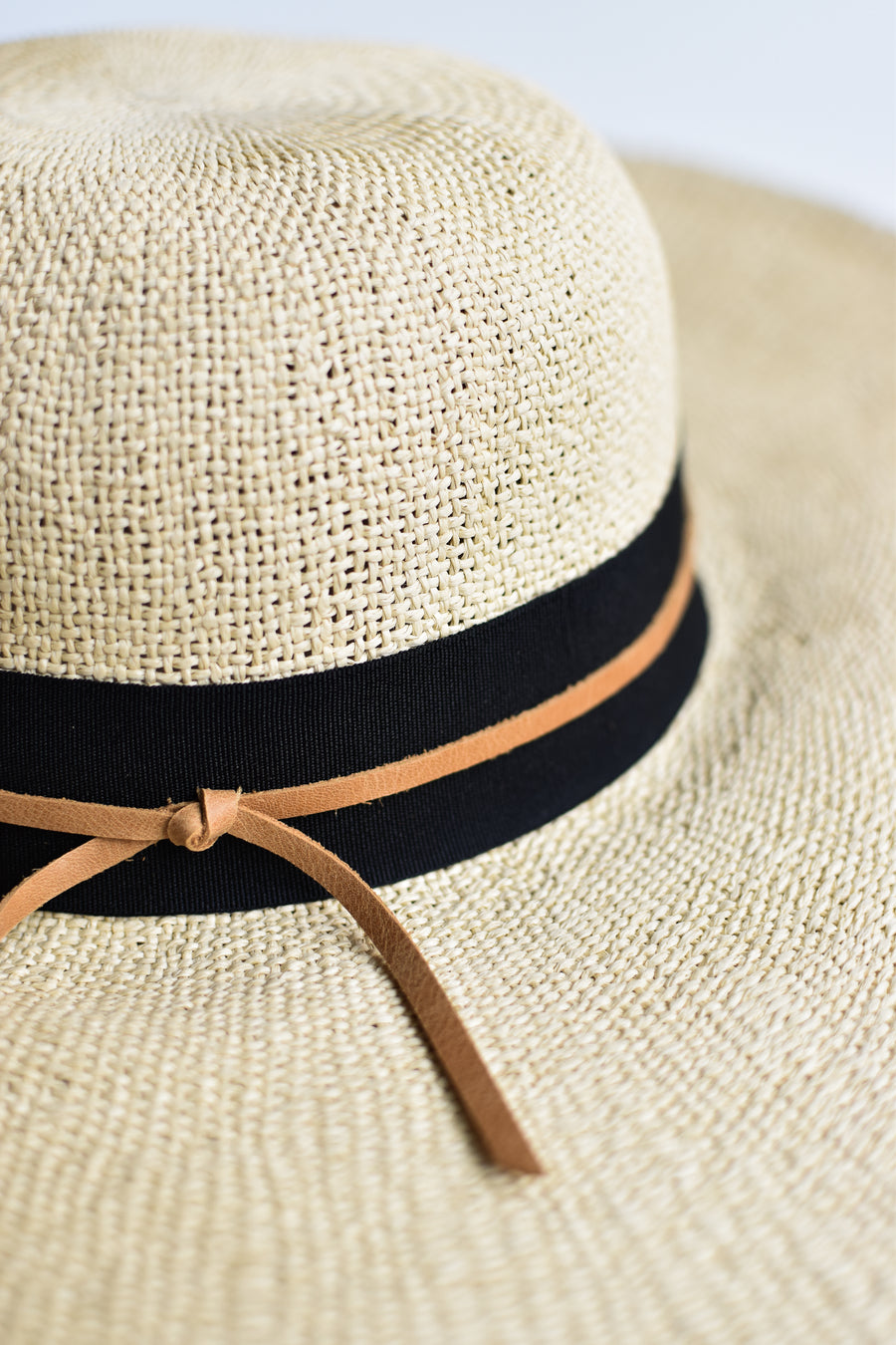 Close up of natural floppy straw hat with black grosgrain ribbon and thin brown leather band.