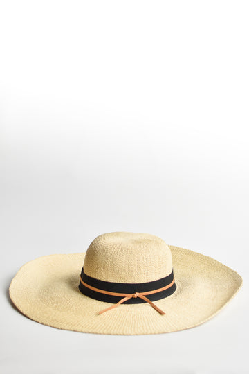 Natural floppy straw hat with black grosgrain ribbon and thin brown leather band.