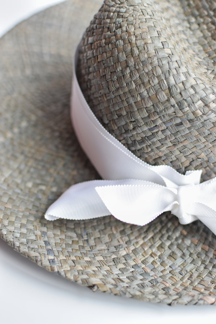 Close up of gray raffia straw panama hat with white grosgrain tie.