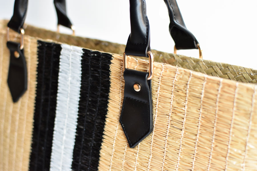 Close up of black leather handle detail on Benicia straw bag.